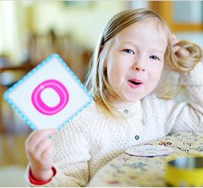 Little girl holding up 'O' Flashcard