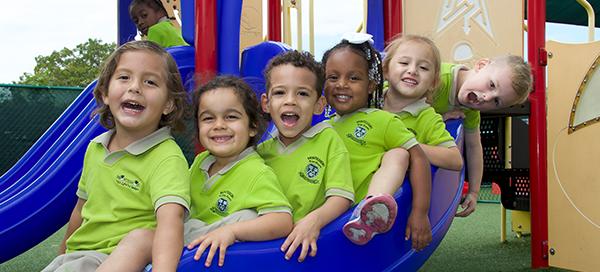 Happy Montessori pre-schoolers on a slide